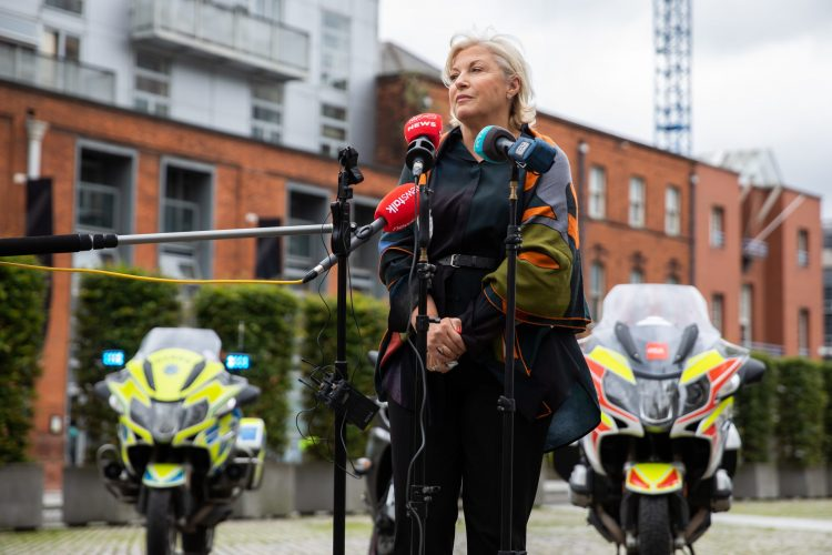 Liz O Donnell speaking into some microphones while standing in front of two Garda motorcycles